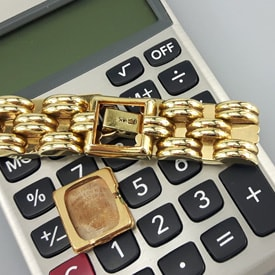 gold watch parts on a calculator