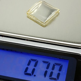 watch crystal weighing on a scale