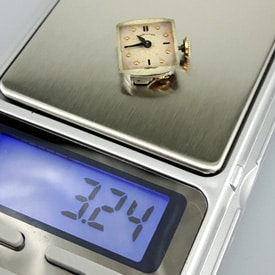 vintage watch movement to be weighed on scale